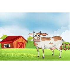 A cow in the farm with a wooden house at the back vector