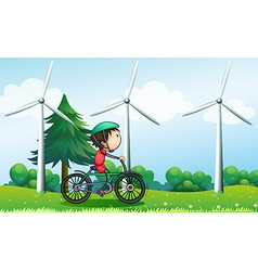 A boy riding with his bike near the windmills vector image