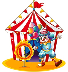 A clown holding balloons near the ring of fire vector image vector image