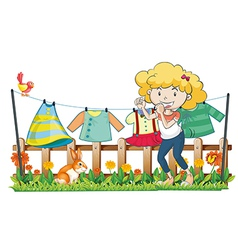 A lady hanging her clothes in the garden near the vector image