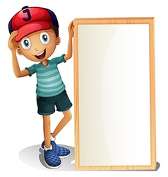 A young boy standing beside an empty signboard vector image vector image