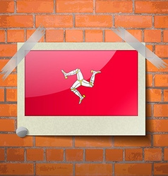 Flags of isle of man scotch taped to a red brick vector