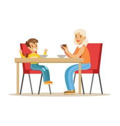 Grandmother having breakfast with boy part of vector