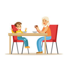 Grandmother having breakfast with boy part of vector