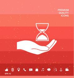 Hand holding hourglass vector