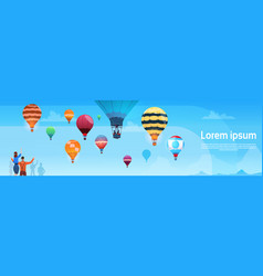 People looking at colorful air balloons flying in vector