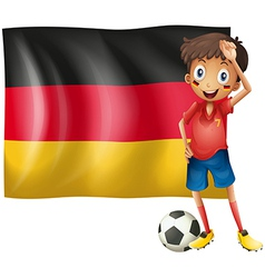 A boy with a soccer ball in front of the flag of vector image vector image