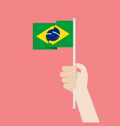 hand holding up brazil flag vector image