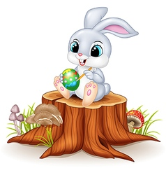 Cartoon easter bunny painting an egg on tree stump vector