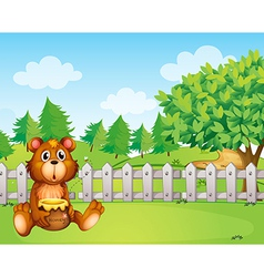 A bear holding a honey at the backyard vector image vector image