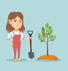 Young caucasian woman planting a tree vector
