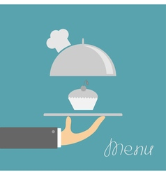 Hand holding silver platter cloche with chefs hat vector image vector image