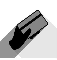 Hand holding a credit card black icon vector