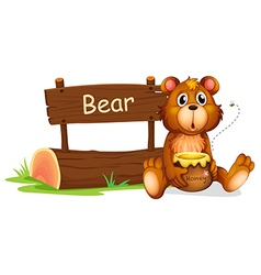 A bear holding a honey beside a wooden signboard vector image vector image