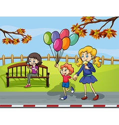 Two girls with a kid holding a balloon in the park vector image