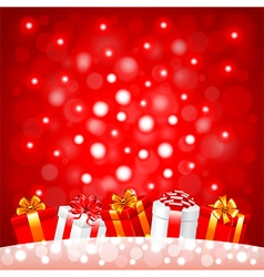 Christmas gifts in the snow on red background vector