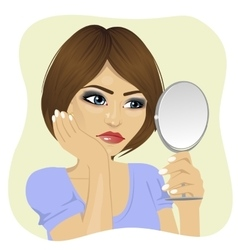 Concerned young woman looking at herself in mirror vector