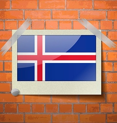 Flags Iceland scotch taped to a red brick wall vector image