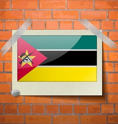 Flags mozambique scotch taped to a red brick wall vector