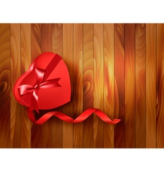 Red heart-shaped gift box with ribbon on wooden vector image vector image