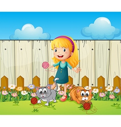 A girl playing with her cats inside the fence vector image vector image