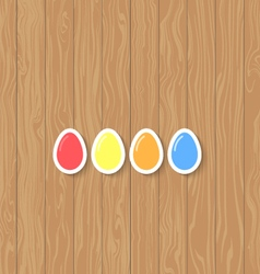 Easter eggs of different colors on a wooden vector image