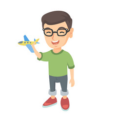 Caucasian cheerful boy playing with a toy airplane vector