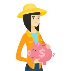 Young asian farmer holding a piggy bank vector