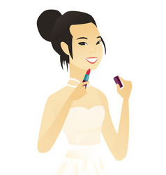 Young asian bride paints lips with red lipstick vector