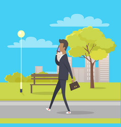Businessman speaks by phone and walks in park vector