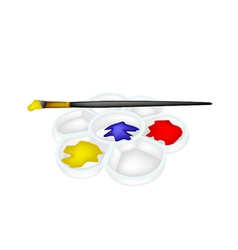 Color paint in plastic palette with artist brush vector