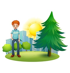 A smiling man standing beside the pine tree vector image