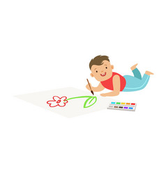 Happy little boy lying on the floor and drawing on vector
