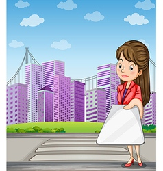 A woman in front of the tall buildings holding a vector