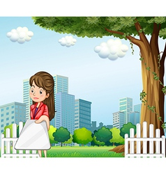 A woman using her gadget in front of the buildings vector image