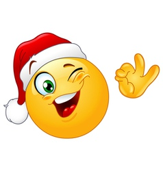 Winking emoticon with santa hat vector