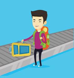 man picking up suitcase on luggage conveyor belt vector image vector image