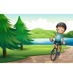 A boy biking near the pine trees at the riverside vector