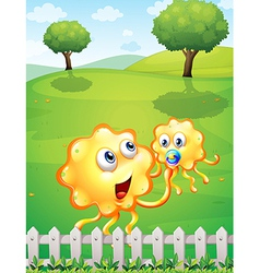 A hilltop with an orange monster playing with a vector image