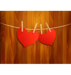 Two red loving hearts hanging on a rope vector image vector image