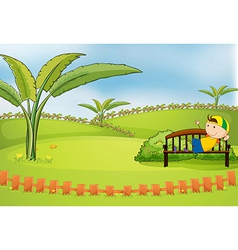 A boy lying at the bench inside the fence vector image