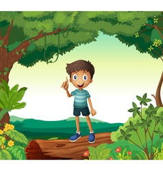 A boy standing on wood in nature vector image