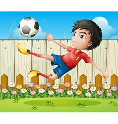 A boy playing soccer inside the fence vector