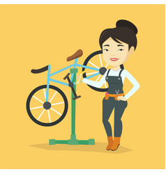 asian bicycle mechanic working in repair shop vector image