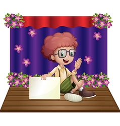 A boy at the stage holding an empty signboard vector image vector image