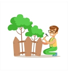 Boy building wooden fence around plants helping in vector