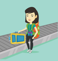Woman picking up suitcase on luggage conveyor belt vector