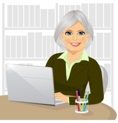 Mature businesswoman working with laptop at office vector