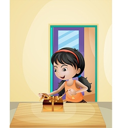 A girl unwrapping a gift vector image