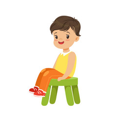 Cute little boy sitting on a small green stool vector